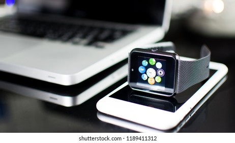 Bangkok, Thailand - Sept 2018: Close up of wrist watches with icons and Gray Aluminum Case, Black Sport Band, Laptop, smartphone. Black fitness watch (activity tracker) on iPhone 6 with Macbook pro