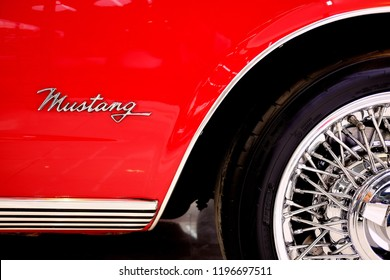 BANGKOK, THAILAND - SEPTBER 17, 2017: Side view of Ford Mustang with reflection on chrome in red background. Vintage American muscle car and  chrome rim