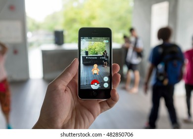 Bangkok, Thailand - September 02, 2016 : Hand of man holding smart phone while playing Pokemon Go capturing Chamander with people in background