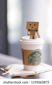 Bangkok, Thailand - September 1, 2018 : A photo of a takeaway cup of Starbucks coffee with cardboard toy character of Danbo sitting on top. In 2018, it operates more than 28,000 branches worldwide.