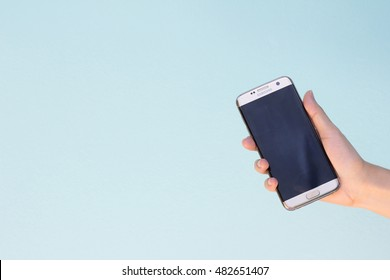 Bangkok, Thailand September 10, 2016 : Woman held android smart phone Samsung galaxy S7 Edge on blue concrete background.