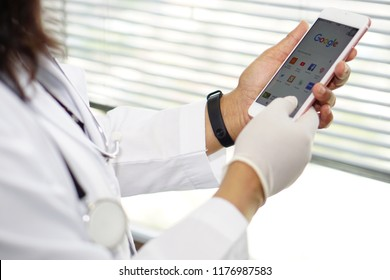 Bangkok, Thailand - September 11, 2018: Asian lady woman doctor holding mobile phone use google website to search data knowledge in nursing hospital ward : healthy strong medical concept.