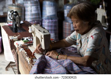 BANGKOK, THAILAND - SEPTEMBER 11: Thai woman sits by the roadside making clothes with a sewing machine in Bangkok. September 11  2017 in Bangkok.
