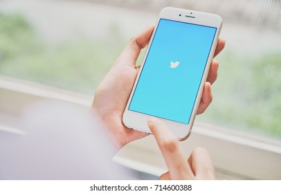 Bangkok, Thailand - September 13, 2017 : Women using phone open Twitter application showing on screen, an online social networking and service that enables users to send and read messages