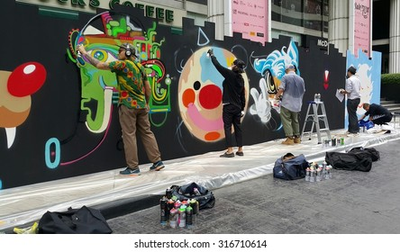 BANGKOK, THAILAND - SEPTEMBER 15, 2015: A group of street artists work on creating their art pieces on a set-up wall for Stronger Together with street arts event near Ratchaprasong intersection.