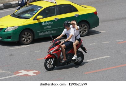 Bangkok, Thailand - September 15, 2018: Young woman not wearing a helmet uses her hands to shield face from sunlight while sitting behind a motorbike