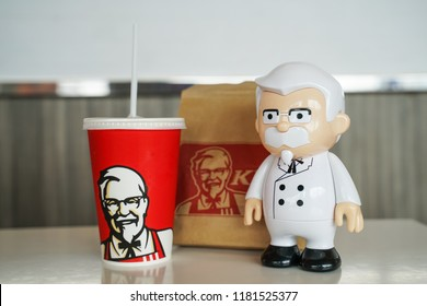 BANGKOK ,THAILAND- September 15,2018: Colonel Harland Sanders statue doll with blurred KFC cold drink and paper bag
