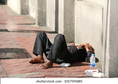 Bangkok, Thailand - September 16, 2016: Homeless man is sleeping on the sidewalk waiting for help from people.