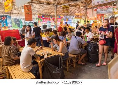 Bangkok, Thailand - September, 16, 2018 :  Unidentified name tourist sitting eat food on a riverbank canal at Khlong Lat Mayom Floating Market Bangkok, Thailand.