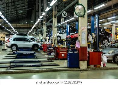 Bangkok / Thailand - September 18, 2018: Mechanics in garage., Mechanics Garage with car on hoist.