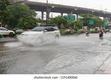 BANGKOK, THAILAND - SEPTEMBER 20, 2018 : Heavy rain in Bangkok, Thailand. effect of raining on the road, Flooding at Bangna, Bangkok. car splashes through a large puddle on flooded street.