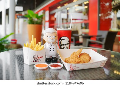 BANGKOK ,THAILAND- September 21,2018: Colonel Harland Sanders  doll with   cold drink , fried chicken and french fried in front of KFC restaurant