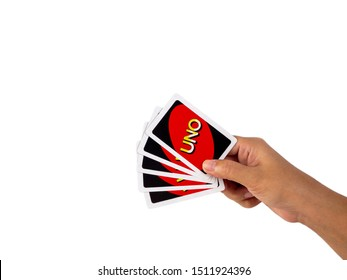 Bangkok, Thailand - September 23, 2018 : Focus of uno cards. Asian woman hold the card with white background. The game for relationship in family or party with friend. clipping path.