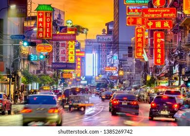 BANGKOK, THAILAND - SEPTEMBER 27, 2015: Traffic on Yaowarat Road passes below lit signs in the Chinatown district at dusk.