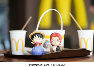 Bangkok, Thailand - September 29, 2018 : A photo of Monkey d. Luffy and Shanks, One Piece character plastic toys from McDonalds' Happy Meal with Coke and fried chicken bucket on the background.