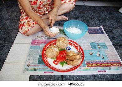 BANGKOK, THAILAND – SEPTEMBER 3, 2017: Old women cooking (scratch coconut) sitting in the terrace, prepare making coconut milk. Coconut on the red tray. Scratched cocunut in the blue plastic bowl.