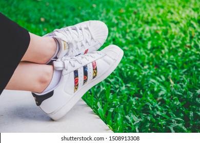 BANGKOK, THAILAND - SEPTEMBER 6, 2019 Women wearing adidas superstar white shoes - grass background