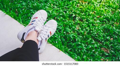 BANGKOK, THAILAND - SEPTEMBER 6, 2019 Women wearing adidas superstar white shoes - grass green background