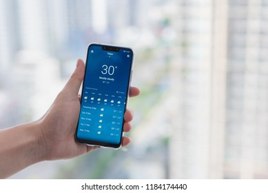Bangkok, Thailand - September 7 2018: Close up a man hand hold Huawei Nova 3 Phone for checking weather forecast at Tokyo with blurred background. To checking weather forecast from internet.