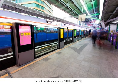 Bangkok, Thailand - September 9, 2019.  Mock up blank digital ads in BTS skytrain station with motion of business people and blur Sky train