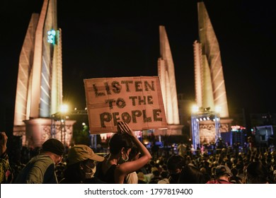 """Bangkok Thailand-Aug16,2020: protester with face mask shows the sign """"LISTEN TO THE PEOPLE"""" at Democracy Monument-Thailand to against the government"""