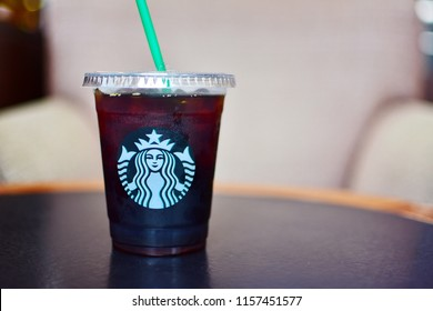 BANGKOK, THAILAND-AUGUST 11, 2018: Starbucks beverage in tall take away plastic glass with Starbucks logo, Iced Americano black coffee with lid and straw on wooden table blurred armchair, copy space