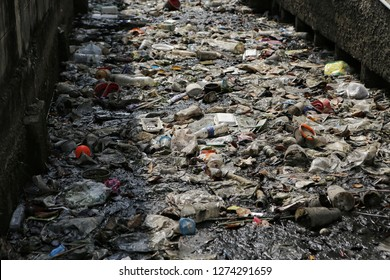 Bangkok, Thailand-CIRCA December, 2018: huge thick area of garbage and dirty litter dumped into canal in Bangkok capital city of Thailand, the dump site is located in the midlle of living area.