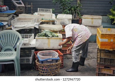 Bangkok, Thailand-CIRCA December, 2018: old elderly lady works alone in her poor vegetable shop at market place, there are a lot of elders still work hard in society with painful job to survive.