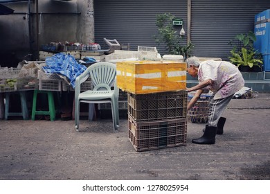 Bangkok, Thailand-CIRCA December, 2018: old elderly lady drag piles of heavy box, works alone at market place, there are a lot of elders still work hard in society with painful job to survive.