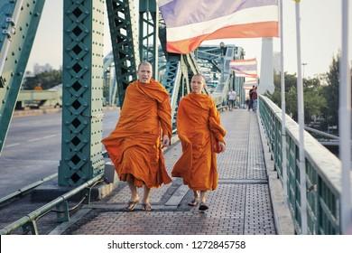 Bangkok, Thailand-circa December, 2018: two buddhist monks walking on the Phra Phuttha Yodfa Bridge, Memorial Bridge in bangkok capital city of thailand. they walk and talk together.