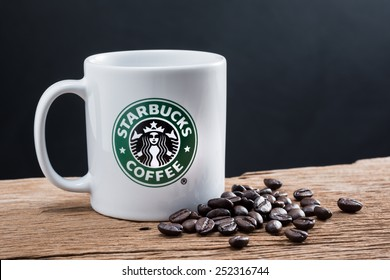 Bangkok ,Thailand-February 12 : Studio still life photography of Starbucks coffee mug with coffee bean on old wood : Starbucks is global brand of coffee drink and very popular in Thailand