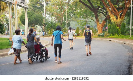 BANGKOK Thailand,January 12,2019 -Thai senior woman on a wheelchair going on a walk with a caregiver with Thai people walking and jogging for exercise in the morning at Lumpini Park.