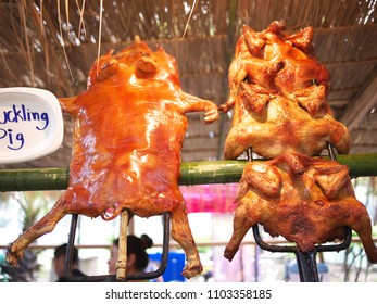 BANGKOK/ THAILAND-JANUARY 17, 2018: Suckling pig and roasted chicken hanging from the dry nipa palm roof, Lumpini Public Park.