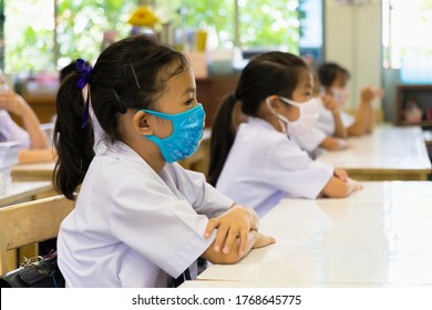 Bangkok, Thailand-July 2,2020: Group of Asian elementary school students and teacher wearing hygienic mask to prevent the outbreak of Covid 19 in classroom while back to school reopen their school.