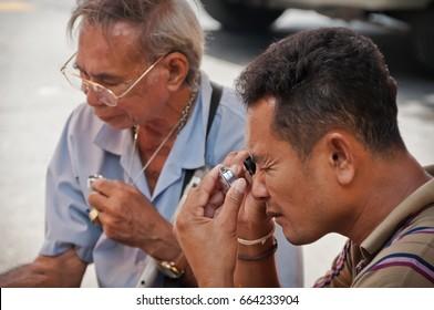 BANGKOK THAILAND-JUNE 19: Unidentified Thai Buddhism inspects on buddha amulets at amulet market on June 19, 2011 in Bangkok,Thailand.