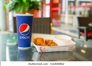 BANGKOK ,THAILAND-June 8,2018:  cold drink in pepsi cup on desk with Kentucky Fried chicken and coleslaw in restaurant