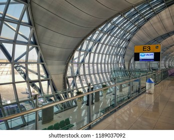 Bangkok, Thailand-March 18, 2018: The transit passage in Suvarnabhumi Airport with window frameworks. There is a boarding zone below with green seats. The stairs with indication sign leads to there