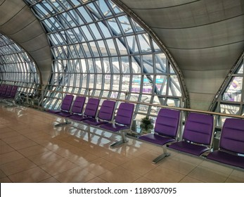 Bangkok, Thailand-March 18, 2018:Transit hall in Suvarnabhumi Airport without passengers.The row of aluminum benches are at the railing separating the hall from oval framed glass wall.