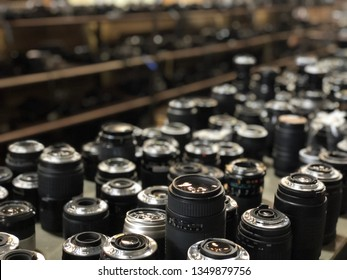 Bangkok, Thailand-March 25,2019 : Close-up of various old slr camera lenses with colorful antireflection multi-layer coating. Different make of cameras on the table. Background of objective with lens