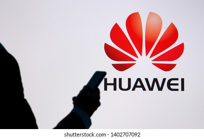 BANGKOK, THAILAND-MAY 20th 2019.Huawei logo on led screen with blurred Silhouette of business man holding mobile phone as foreground