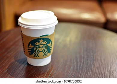BANGKOK, THAILAND-MAY 24, 2018 : Starbucks hot beverage in tall cup size with paper holder of Starbucks logo, coffee, tea or chocolate on wooden table with some interior at shop with copy space