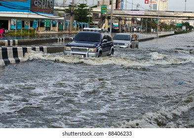BANGKOK, THAILAND-NOVEMBER 8: Cars and trucks navigate through the flood after the heaviest monsoon rain in 20 years in the capital on  November 8, 2011   Ngam Wong Wan Road, Bangkok, Thailand.