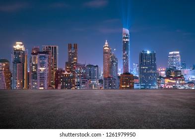 Bangkok urban cityscape skyline night scene with empty asphalt floor on front
