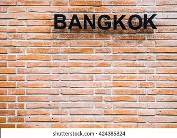 Bangkok word sign on top right corner of brick wall