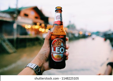 BANGKOK0, THAILAND - JUNE 17 , 2018: handed bottle of cold Leo beer on dark brown bacony with water drop and blurred colorful light bokeh in background, selective focus.