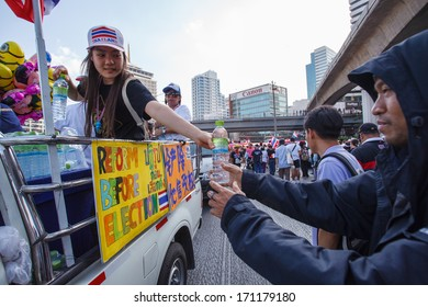 BANGKOK-JAN 13: Unidentified Thai protestors give free drinking water to other protestors in mob that resistant to government of Shinawatra regimes on Jan 13, 2014 in Bangkok, Thailand.