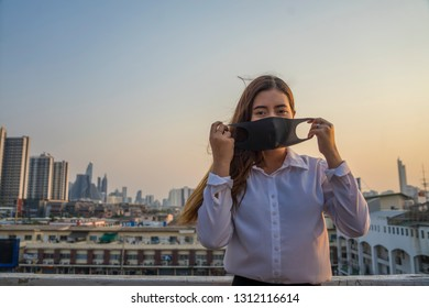 Bangkok's air quality has fallen to harmful levels with the quantity of unsafe dust particles. Asian Businesswomen wearing masks protect dust in the air are polluting the capital of Bangkok.