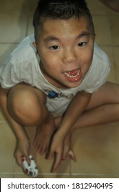 Bangkok,Thailand - 11/09/2020: Down symdrome  boy,he's type Alfi's syndrome  intellectual prominent forehead, broad flat nasal bridge,  ,squint eye looking and cute smile for take photo portrait.