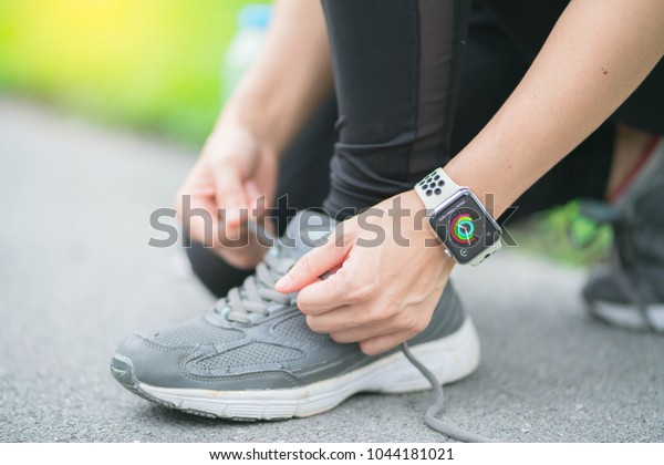 Bangkok,Thailand ,12 mar 2018 : Asia woman sport ware tying sport shoes ready for run with apple watch smart watch
