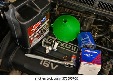 Bangkok,Thailand - 16 Dec 2015:The equipments for refiling motor oil(Amsoil Signature 5w30) in the car engine(Chevrolet Aveo), ACDELCO oil flter, Oil Filter Cap Wrench, funnel and socket wrench(Koche)